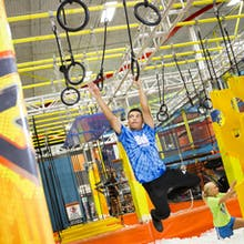 Boy on warrior course rings obstacle