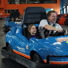 Man and daughter enjoy a go-kart race