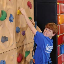 Boy climbing our Urban Air indoor climbing wall